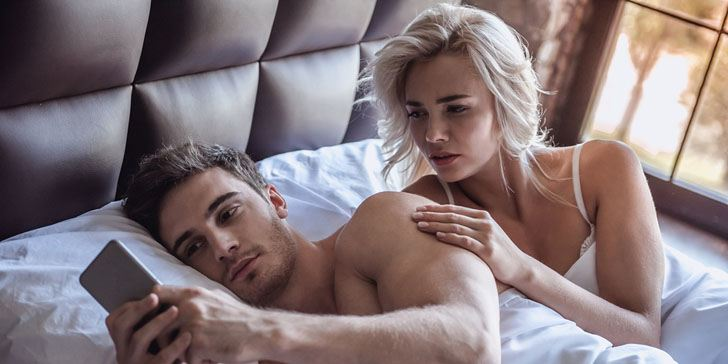 Beautiful young couple is lying in bed guy is using a smart phone girl is looking with reproach