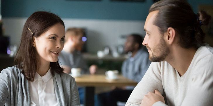 Happy millennial couple in love talking sitting at coffee house table together, smiling young attractive man and woman chatting and flirting enjoying pleasant conversation, date in cafe concept